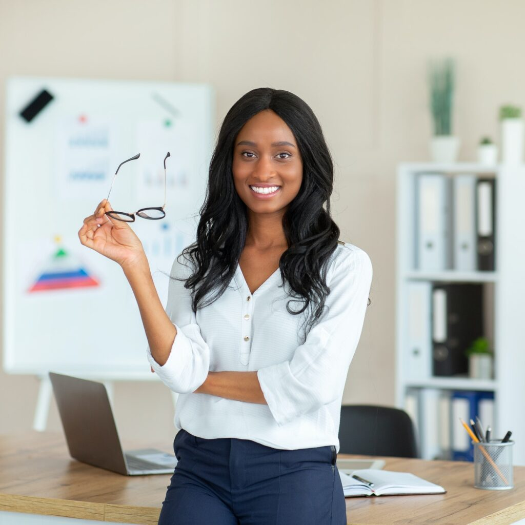 Portrait of positive black business lady smiling and looking at camera in her office