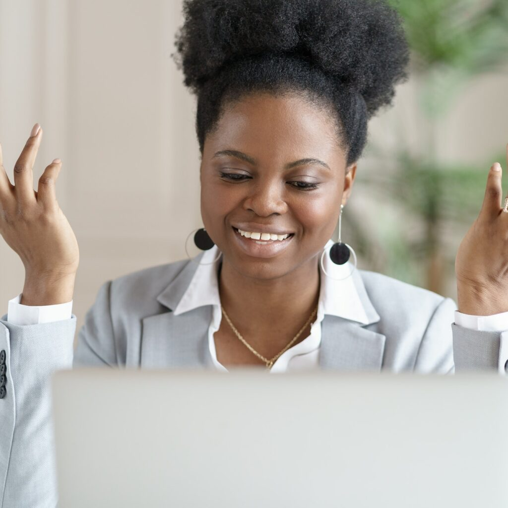 Smiling African business woman watching education webinar, talking on video chat or videoconference