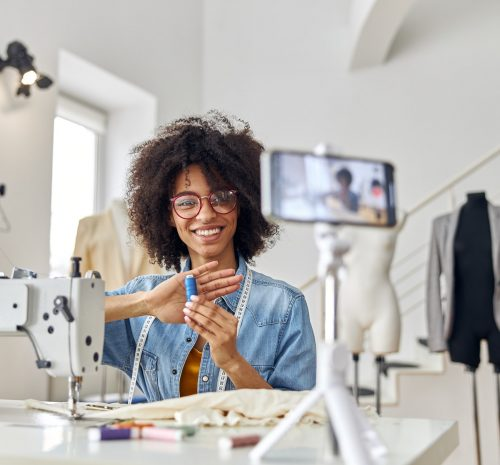 African-American lady holds blue threads shooting tutorial at sewing machine in workshop